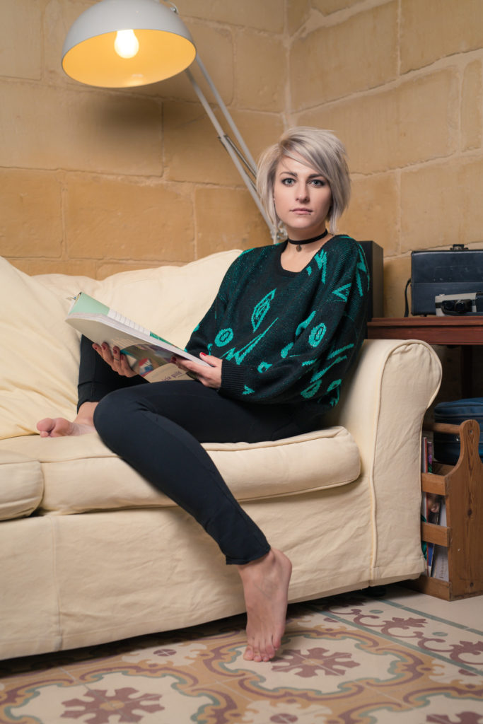 Model, Sacha, seated on a couch facing camera, wearing the retro black and green sweater.