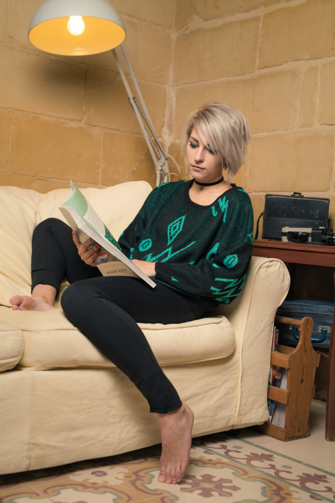 Model, Sacha, seated on a couch holding a magazine, wearing the retro black and green sweater.