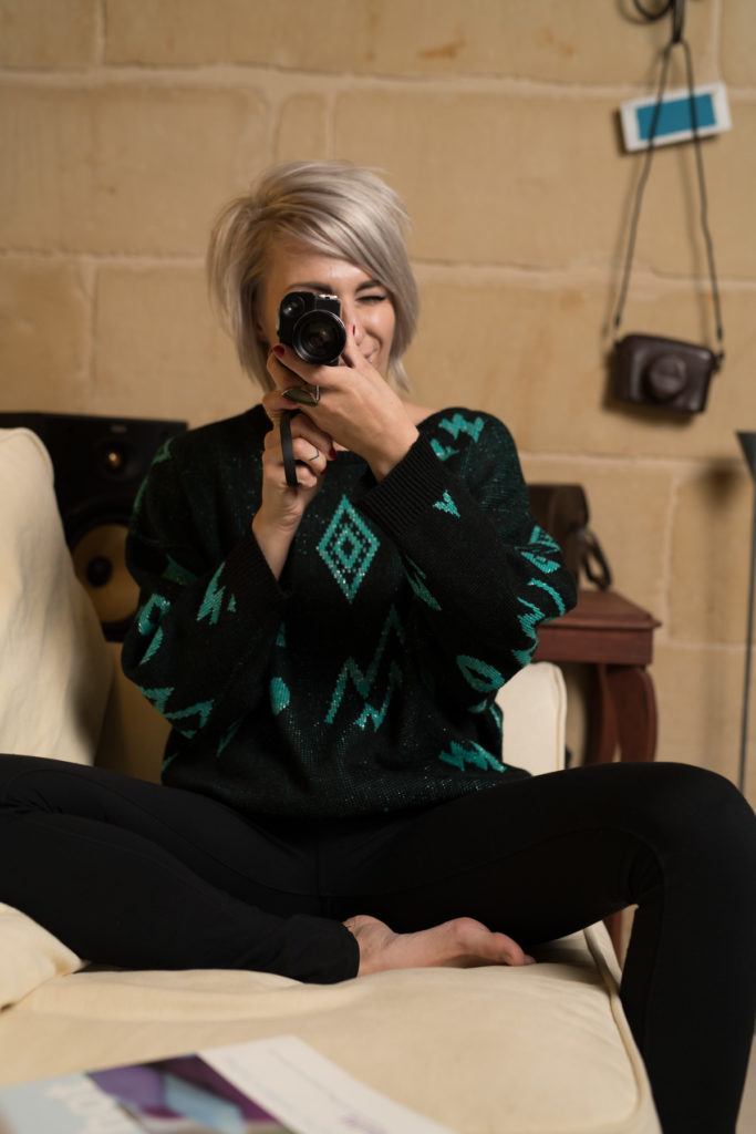 Model, Sacha, wearing the retro black and green sweater and looking through a vintage camera.