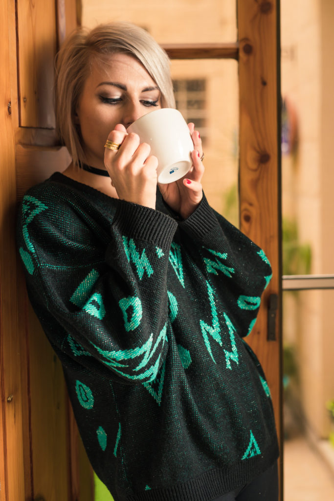 Model, Sacha, wearing the retro black and green sweater and sipping coffee from a white mug.